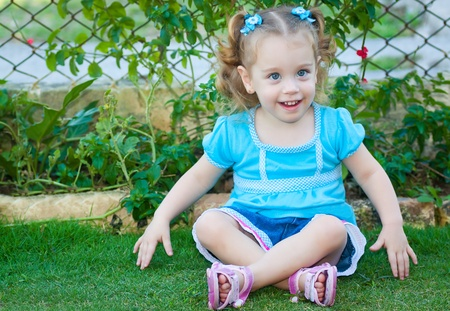 Beautiful small girl with gorgeous blue eyes and blonde curly hair sitting on the grass photo