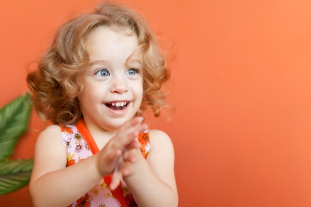 people clapping: Portrait of a beautiful small girl with gorgeous blue eyes and blonde curly hair clapping her hands on an orange background Stock Photo