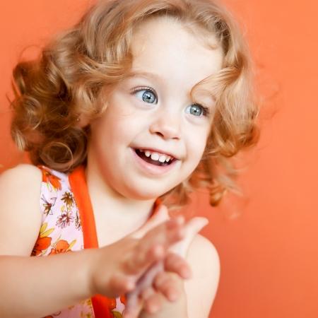 manos aplaudiendo: Retrato de una hermosa niña pequeña con hermosos ojos azules y pelo rubio rizado aplaudiendo sobre un fondo naranja