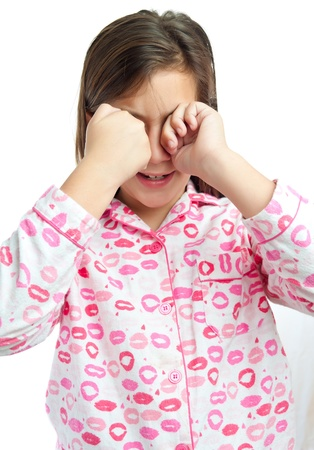 Sleepy young girl wearing pajamas isolated on a white background photo