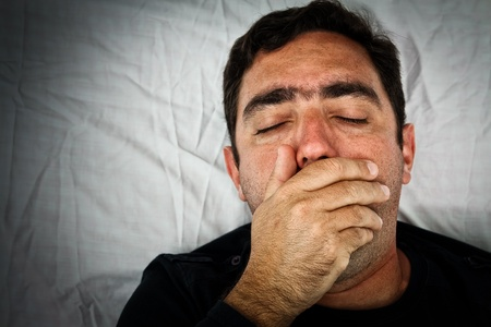 Grunge portrait of a sick hispanic man laying in bed covering his mouth to avoid coughing or vomiting photo