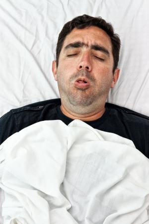 Portrait of a sick hispanic man laying in bed and coughing photo