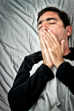 Grunge portrait of a sick hispanic man laying in bed covering his mouth to avoid coughing or vomiting