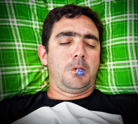 Grunge portrait of a sick hispanic man laying in bed with a thermometer in his mouth photo