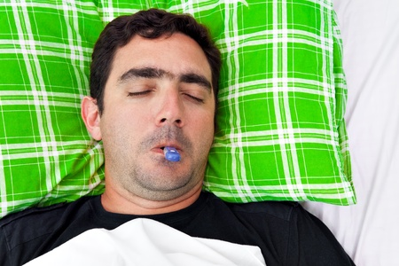 Portrait of a sick hispanic man laying in bed with a thermometer in his mouth and his eyes closed Stock Photo - 12156434