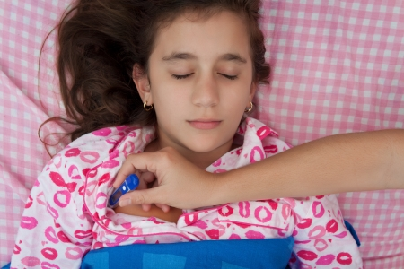 Portrait of a beautiful hispanic girl sick with fever while a hand with a thermometer measures her temperature photo
