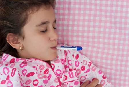 Portrait of a beautiful hispanic girl sick with fever with a thermometer in her mouth laying on a bed with pink sheets Stock Photo - 12156440