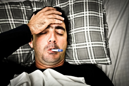 fever: Dramatic desaturated image of a sick man laying in bed with fever