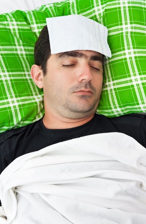 forehead: Sick hispanic man laying in bed with a tissue in his forehead to relieve him from fever or headache