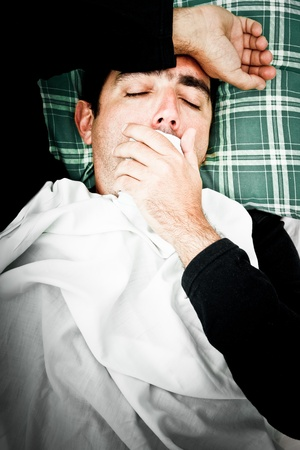 Dramatic desaturated image of a sick man laying in bed and coughing with a handkerchief in his hand Stock Photo - 12156436