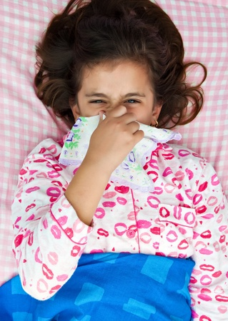 Hispanic girl blowing her nose and laying in her bed wearink pink pajamas photo