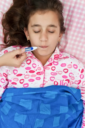 Cute hispanic girl sick with fever laying in her bed with a thermometer on her mouth photo