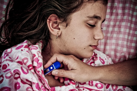 Grunge sad image of a small girl sick with fever while a hand with a thermomter mesures her temperature photo