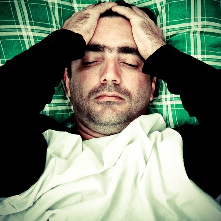 mentally: Dramatic image of a very stressed or mentally disturbed man suffering a headache laying in bed Stock Photo