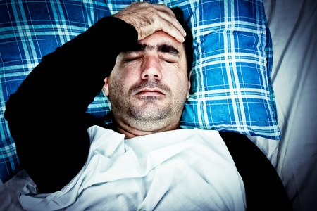hospital stress: Dramatic image of a very stressed or mentally disturbed man suffering a headache laying in bed Stock Photo