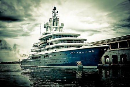 luxury yacht: Grunge image of a modern scientific research or tourism ship docked in a pier with a violent storm approaching