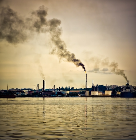 An oil refinery polluting the atmosphere with a huge smoke column pictured at sunset Stock Photo - 12450844
