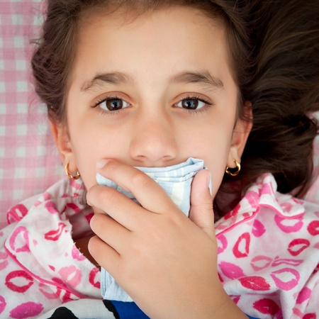 Portrait of a small girl sick with the flu covering her mouth with a handkerchief photo