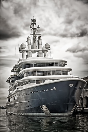 Grunge desaturated view of a modern scientific research or tourism ship docked in a pier with a violent storm approaching Stock Photo