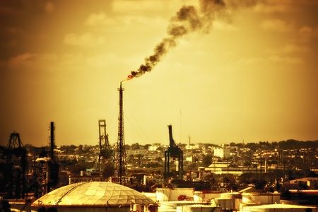 polluting: Flame from an oil refinery polluting the atmosphere with a huge column of black smoke Stock Photo