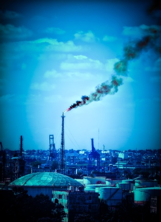 gritty: Flame from an oil refinery polluting the atmosphere with a huge column of black smoke Stock Photo