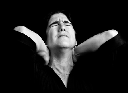 Black and white portrait of a stressed woman suffering from neck pain on a black background photo