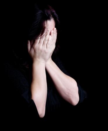 mujer llorando: Dramático retrato de una mujer joven llorando y tapándose los ojos sobre un fondo negro con espacio para texto