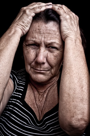 Grunge portrait of an old woman with her hands on her head and a desperate expression on a black background photo