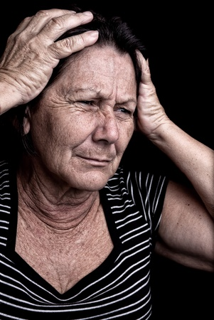 Grunge portrait of an old woman with her hands on her head and a desperate expression on a black background