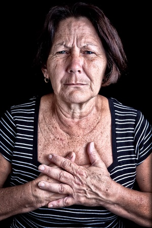 heart disease: Mature woman suffering from chest pain or depression on a black background