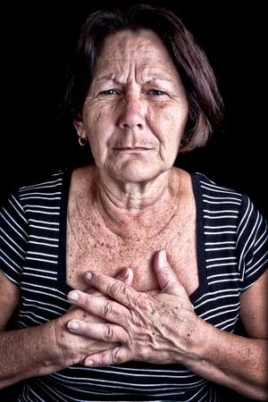 heart disease: Mujer madura que sufre de dolor en el pecho o la depresión en un fondo negro Foto de archivo