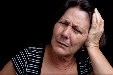 Aged woman suffering from a strong headache on a black background with space for text Stock Photo - 12748185