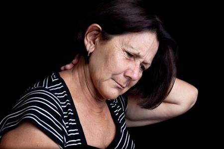 dolor muscular: Mujer madura que sufre de dolor de cuello o el hombro sobre un fondo negro con espacio para texto