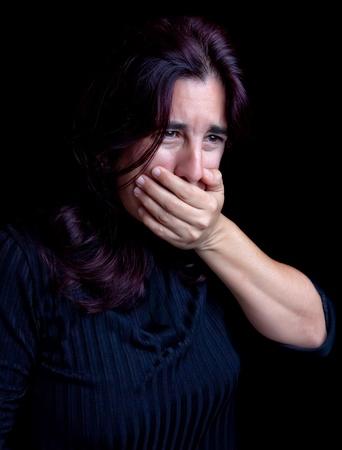 tosiendo: Mujer joven tapándose la boca para evitar la tos o vómitos en un fondo negro con espacio para texto