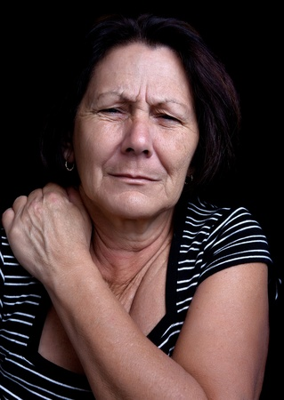 Portrait of a senior lady suffering from shoulder pain on a black background Stock Photo - 12748189