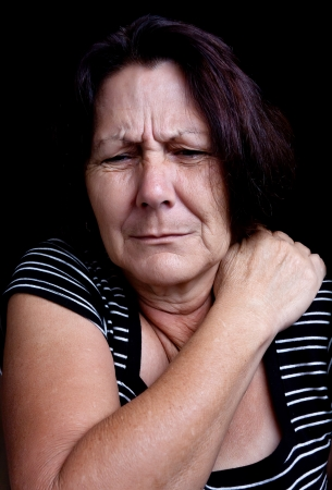 Portrait of a senior lady suffering from shoulder pain on a black background photo