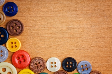 Colorful sewing buttons creating a frame on a wooden background with space for text photo