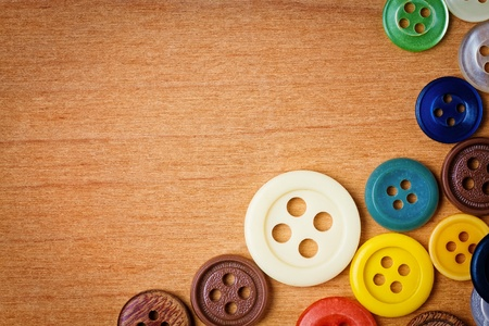 accesory: Colorful sewing buttons creating a frame on a wooden background with space for text