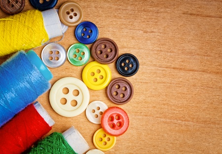 cloth manufacturing: Colorful sewing buttons and thread reels on a wooden background with space for text
