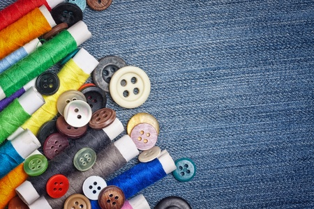 Set of colorful  sewing buttons and thread reels creating a frame   on a blue denim fabric with space for text photo