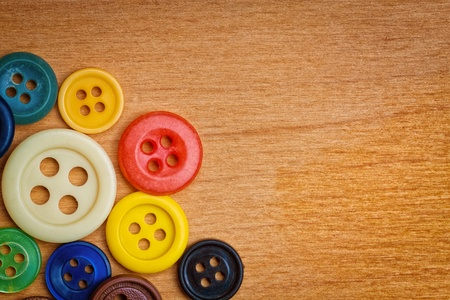 Set of round colorful sewing buttons creating a frame on a wood background  with space for text photo