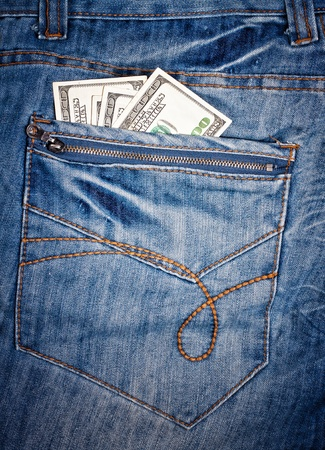 Macro shot of trendy jeans with american 100 dollars bills on its pocket photo