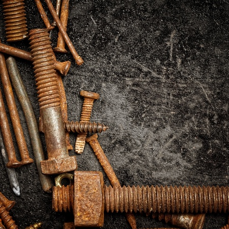gritty: Nuts,bolts and nails on a textured metallic background with space for text Stock Photo