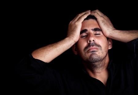 persona triste: Retrato de un joven estresado y triste, con una expresi�n dram�tica sobre un fondo negro