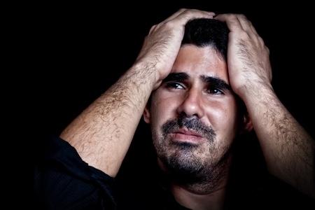 Portret van een gestresste en droevige jonge man met een dramatische uitdrukking op een zwarte achtergrond