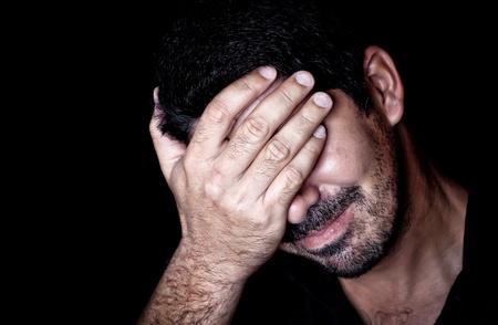 cara triste: Retrato de un hombre muy estresado joven que sufre un dolor de cabeza y cubri�ndose la cara sobre un fondo negro Foto de archivo