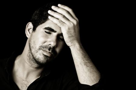 Imagen monocromática de un joven apuesto hombre hispano preocupado o tiene un dolor de cabeza aislado en negro