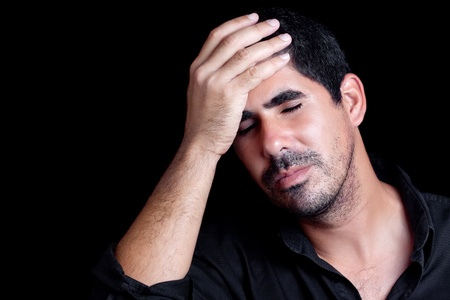 Young handsome hispanic man worried or having a headache isolated on black photo