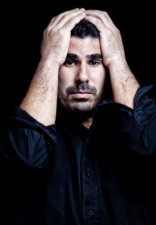 Young hispanic man suffering a headache or a very strong stress or depression isolated on black photo