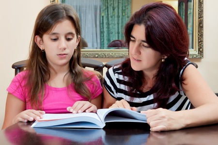 Beautiful hispanic girl and her young mother reading a book together or studying at home photo